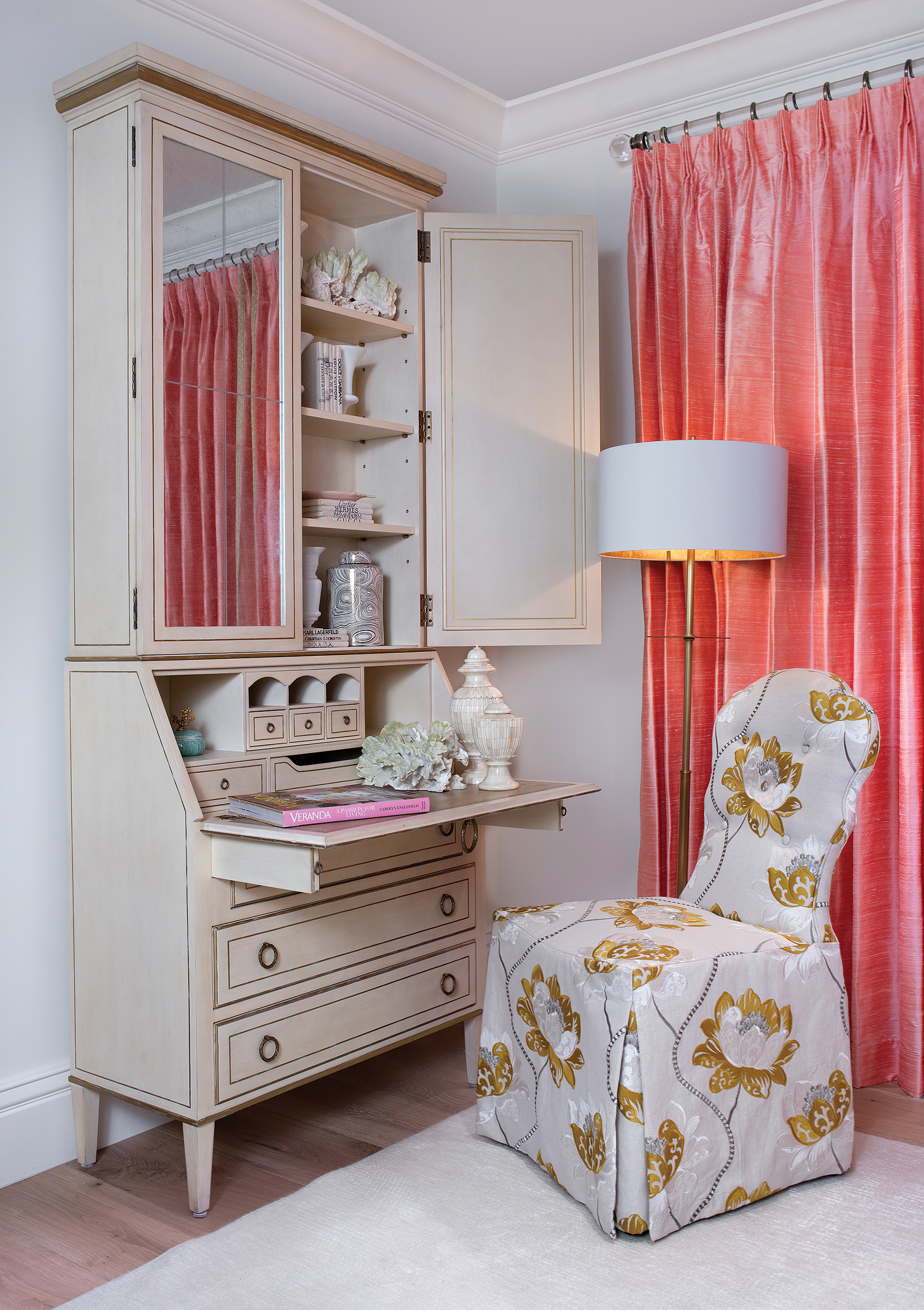 The Leif secretary desk with an Antique Linen finish is a staple of August's line. An Arden Court chair with imported fabric completes this cozy workspace. French doors dressed in coral draperies fabricated by Statewide Window Treatments open onto the travertine pool deck. Flowers shown are courtesy of the Naples Garden Club.