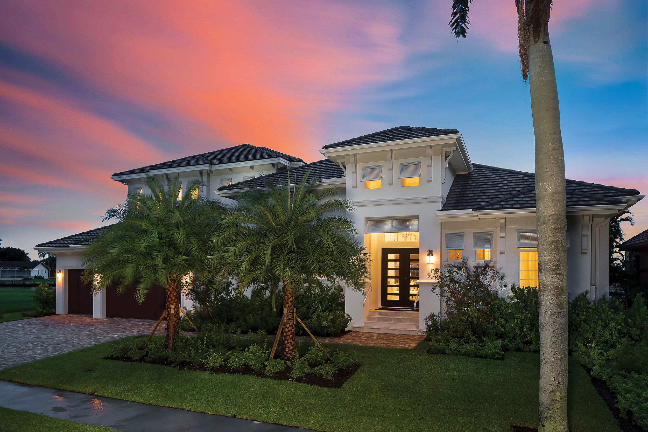 The home's inviting exterior, created by Southwest Florida Design, is a beautiful blend of West Indies style and classic Florida charm. The home is balanced but not symmetrical, creating a more casual appeal perfect for its island location. Accents like the corbels and louvered awnings over the windows add visual interest and are in keeping with the tropical aesthetic. The lush landscaping that surrounds the house creates the feeling of an oasis and the combination of mature and new trees helps balance this new construction home.