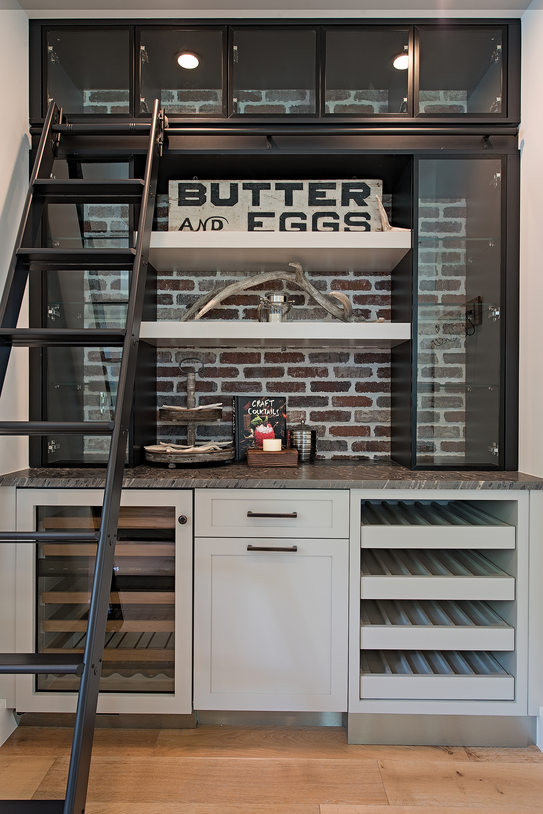 he whimsical library ladder and open shelving adds a fun element to the bar area in the kitchen. The wine cooler and storage racks create the perfect launching pad for a night of entertaining.
