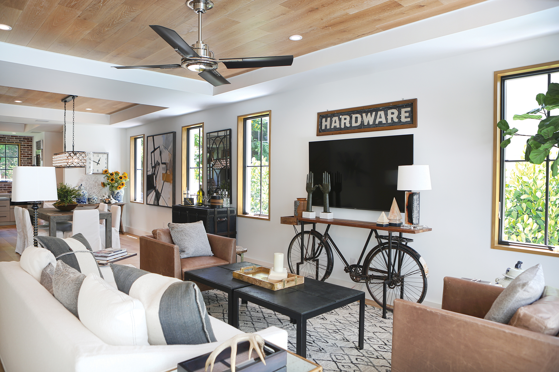 In the living room, the unique media stand was created from an old bicycle and enhances the urban loft feel of the home while giving a nod to the bikeable streets of Old Naples. A mix of leather and linen-covered furniture creates a beautiful seating arrangement. Here, the natural wood-cased windows add to the character of the home as they let the Florida sunshine through. This room is also adjacent to the pool area and courtyard so the new owners can easily take advantage of the outdoor space beyond.