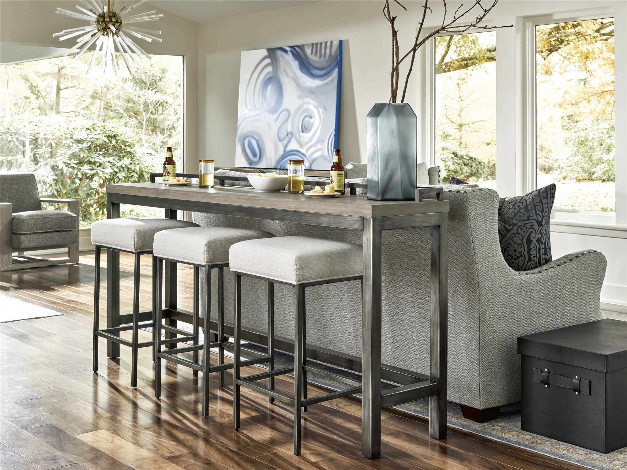 Placing a simple Parsons-style counter height table with tucked-away stools at the back of a couch can add two to three additional seats, while serving as a sofa table or even desk when not in use for dining.