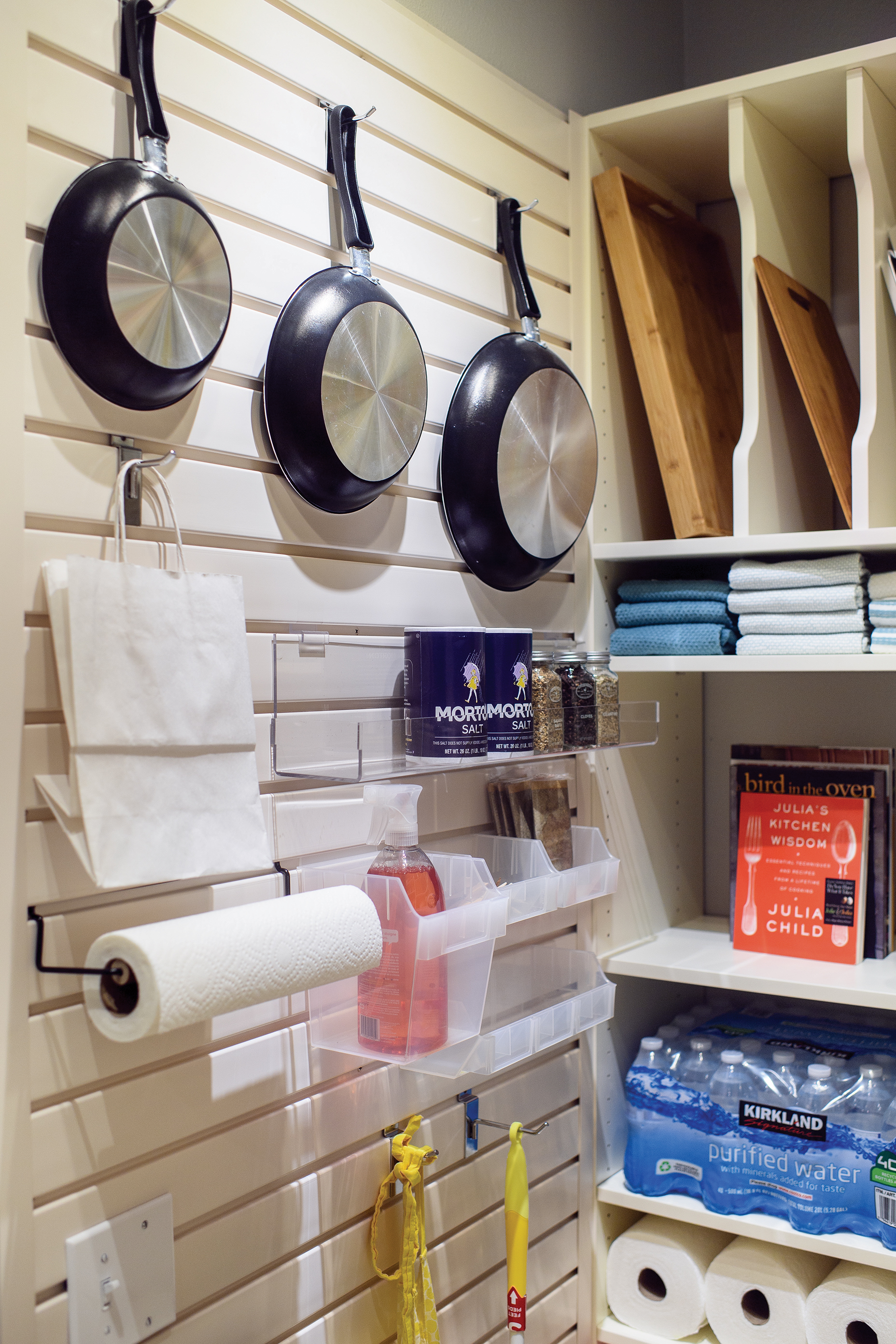 Make a clean sweep of your pantry with a customizable slat wall for storage cleaning supplies and implements.