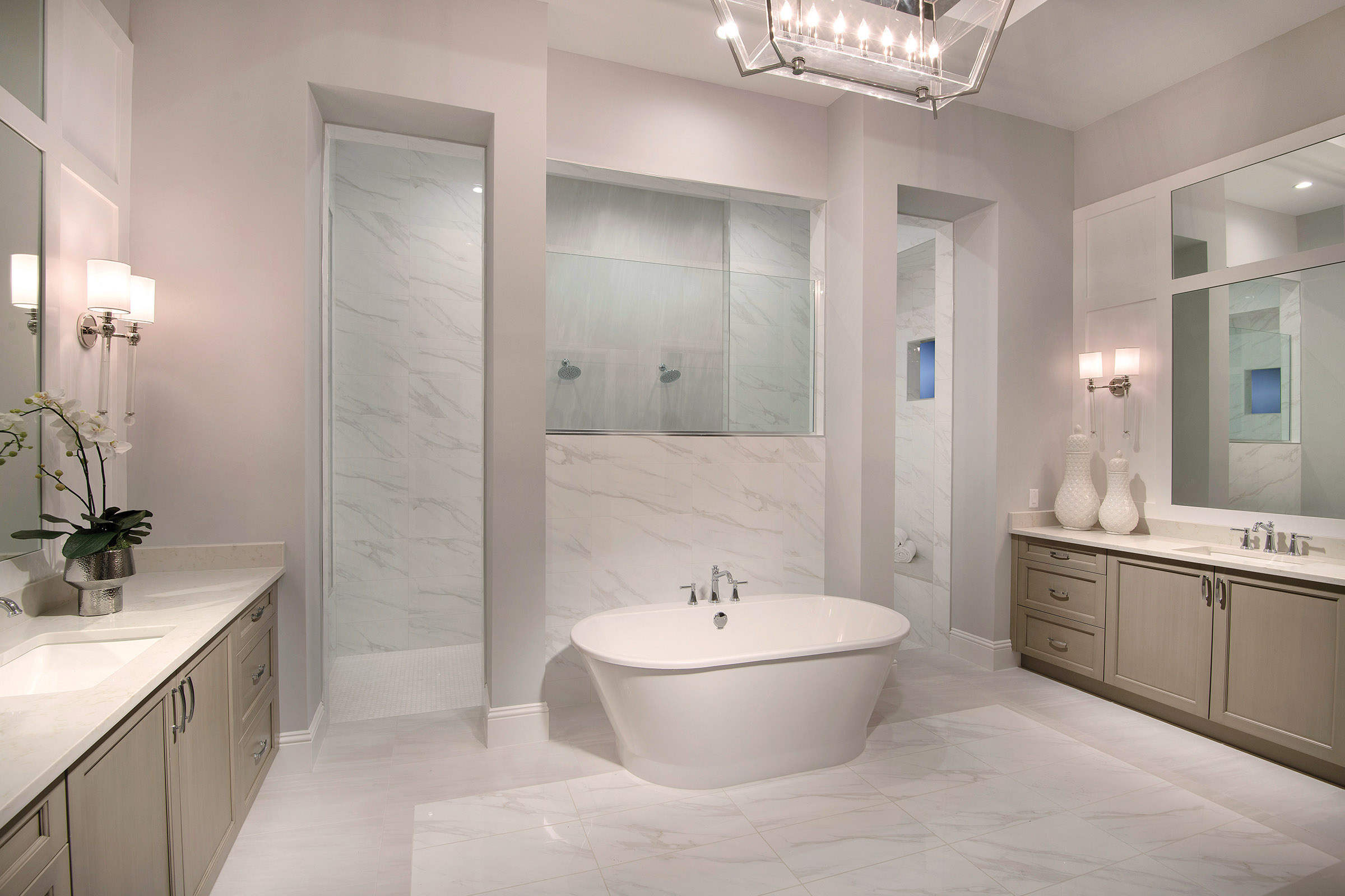 The free-standing soaking tub and tile and glass accent wall is the focal point in the master bath. Behind the walk-in shower, there are dual seats, modern shower features, and decorative tile accents. His and hers matching vanities, topped with large quartz counters, feature custom framed mirrors and sconce lighting.