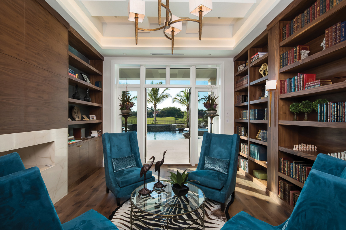 The home's library features modern, dark wood built-in shelves and cabinets which are juxtaposed by the bright colors of the four accent chairs and fun lighting choices. Here, the other side of the see-through fireplace is visible and has been clad in walnut with stone facing.