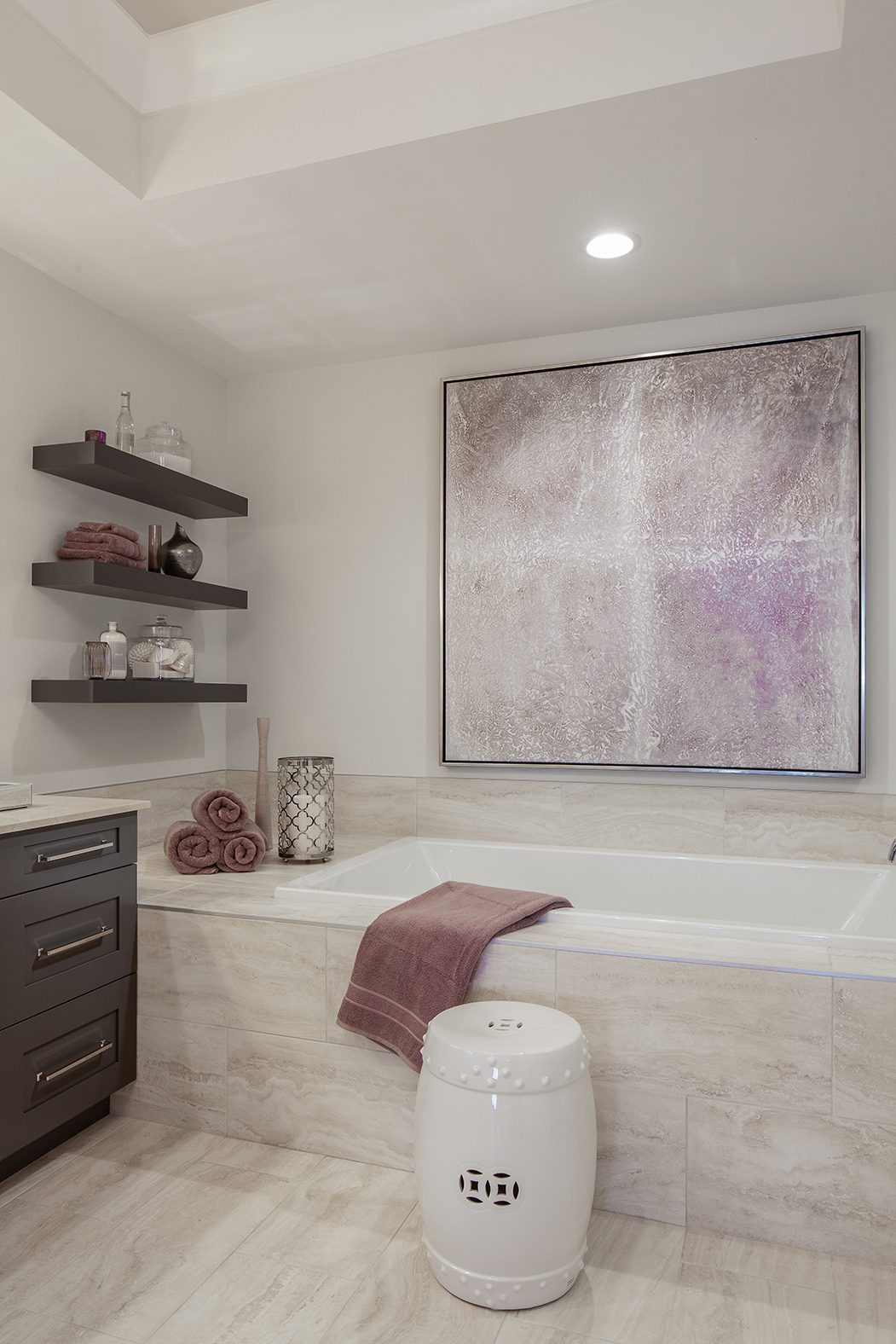 """Purple holds a great deal of sentimental value to the couple I worked with in this unit and they always weave it into their home no matter where they are located,"" says Hall. Here, she used the color in a comfortable bathroom. Artwork over the tub incorporates the color and creates the base palette for the room. From there, she uses open shelving for a spa-like feel and added glass elements for sparkle and glamour. The espresso cabinets and shelves bring out the purple and warm the space."