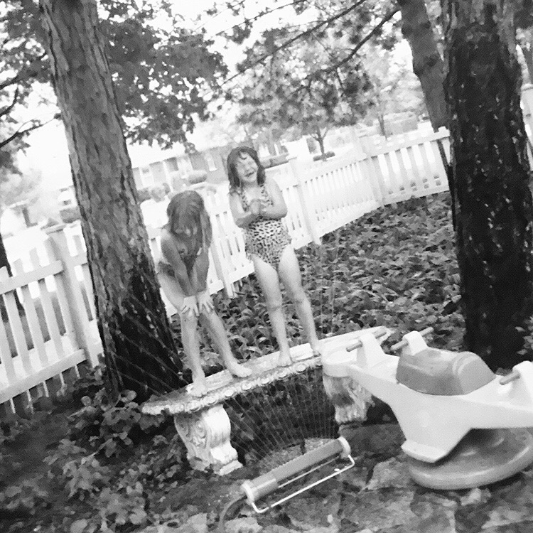 "Yesterday my mom sent me this photo of my cousin Rachel and I in her backyard. I was immediately taken back to a flood of memories, my cousins side yard, the sleepovers and family meals, the garage sales and late nights begging for 'just one more hour"". The simplicity of our humble beginnings as a crazy family.  After seeing this photo I can remember all these moments & how they felt, at some point in being an adult I forgot about this joy I had as a child… like standing on a bench getting sprayed with water, and all the fleeting memories we had growing up. It made me want to find away to bring this little girl with her hands on her knees laughing back into my everyday…to experience life freely.   When my mom sent me this photo & the feeling that washed over me, completely touched to why Our Days is so important. The days you are experiencing right now as a family, will be cherished in a very tangible way as your children pick up the photographs and are taken back to the here & now with such joy and gratitude. Don't miss these moments, they mean more than you even know.  - Jessica Eileen"