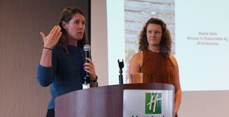 Board member Sophie Neems (right) presented Shanti Sellz with the 2018 Woman in Sustainable Agriculture Award.