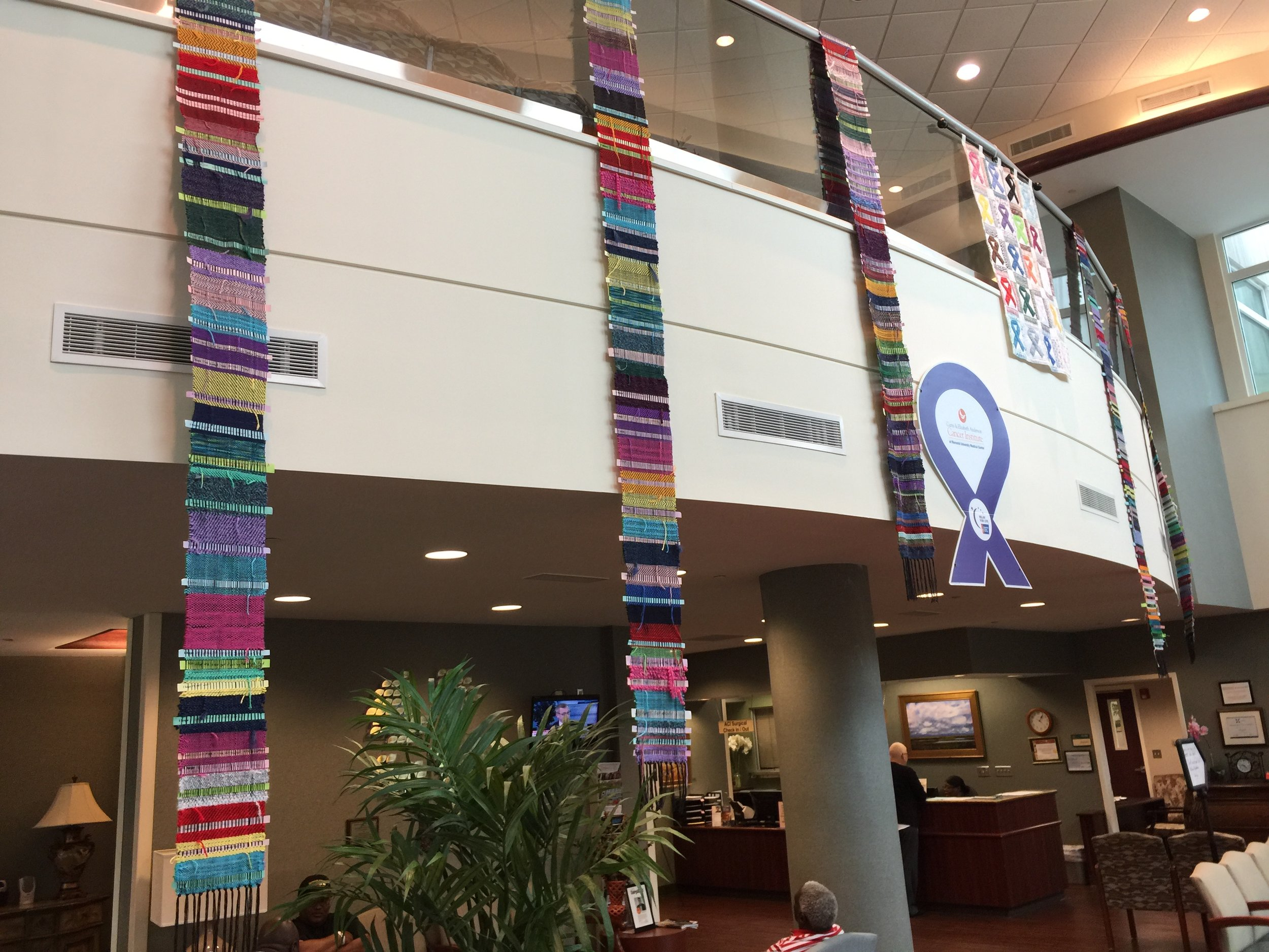 Weaving HOPE - Members of the Fiber Guild of the Savannahs have been working on the Weaving HOPE project at the Anderson Cancer Institute at Memorial Hospital.  Using donated colorful yarns on a simple cotton carpet warp members encourage patients and caregivers to help weave banners than hang in the atrium waiting room. One of the guild's portable 4 shaft Dorset looms is loaned to the institute for this project.  Those waiting are encouraged to complete the sentence