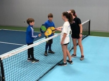 Just what IS pickleball? - PICKLEBALL IS A RACQUET SPORT WHICH COMBINES ELEMENTS OF TENNIS, BADMINTON AND PING PONG. IT'S PLAYED ON A COURT MUCH SMALLER THAN THE SIZE OF A TENNIS COURT. PLAYERS USE A PADDLE AND A WIFFLE BALL.