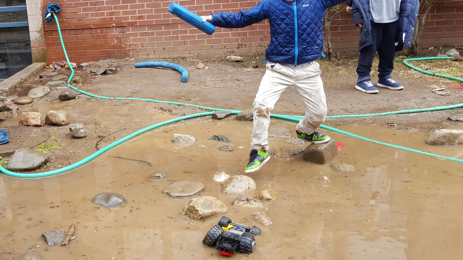 A child steps gingerly from one rock to another, maneuvering above a flooded muddy area. Another child stands on not flooded ground nearby, and a green hose snakes its way around the background of the image, and a toy truck sits partly submerged in the puddle in the foreground.
