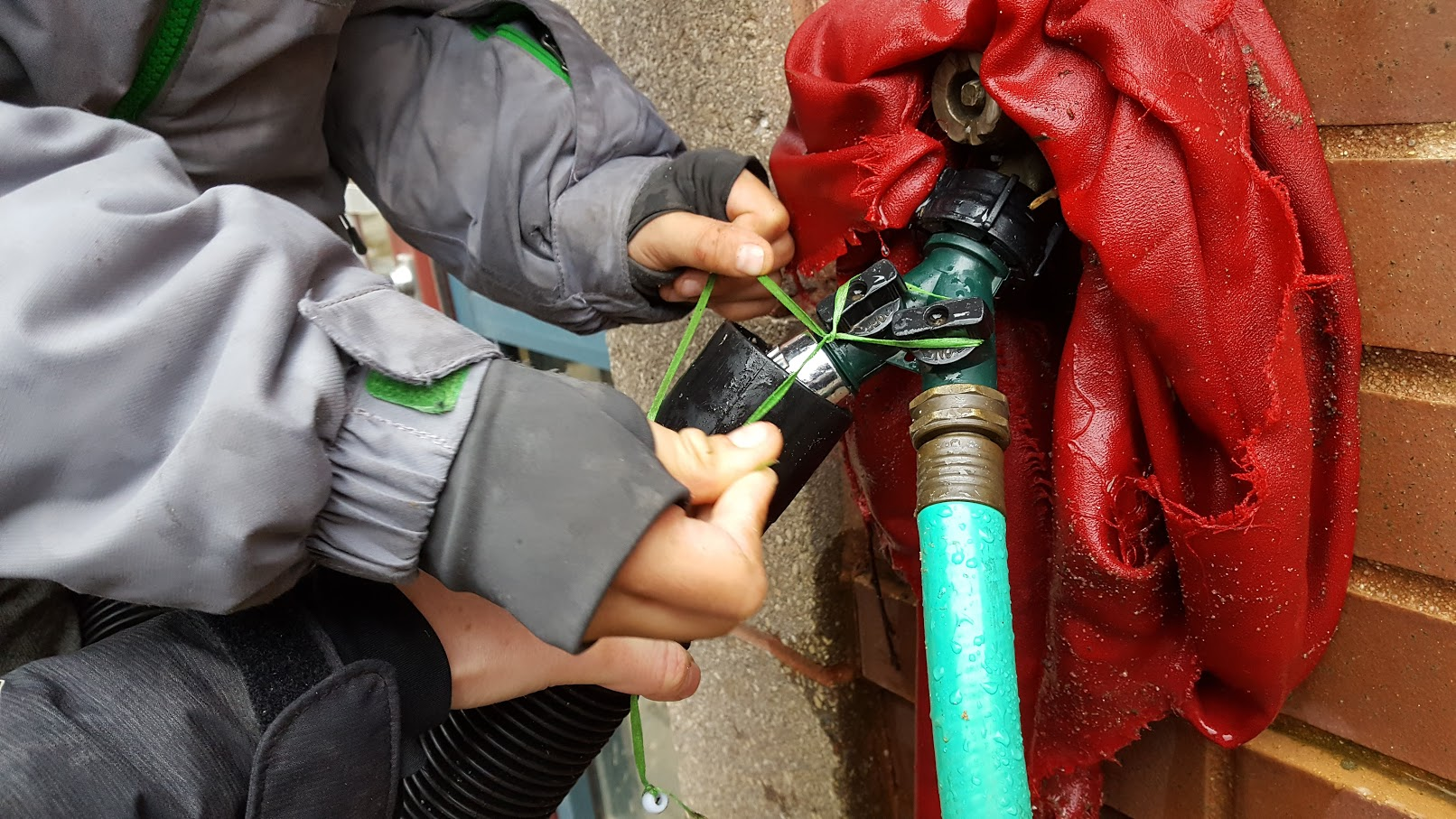 Closeup of a hose attached to a faucet on a brick and concrete wall. a child's hands maneuver some string around the knobs of the faucet.