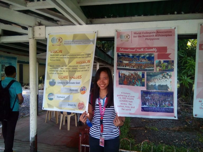 Shelaine posing with the posters used to promote CARP