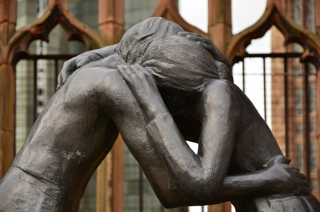 """A sculpture of two people embracing with the title """"Reconciliation."""""""