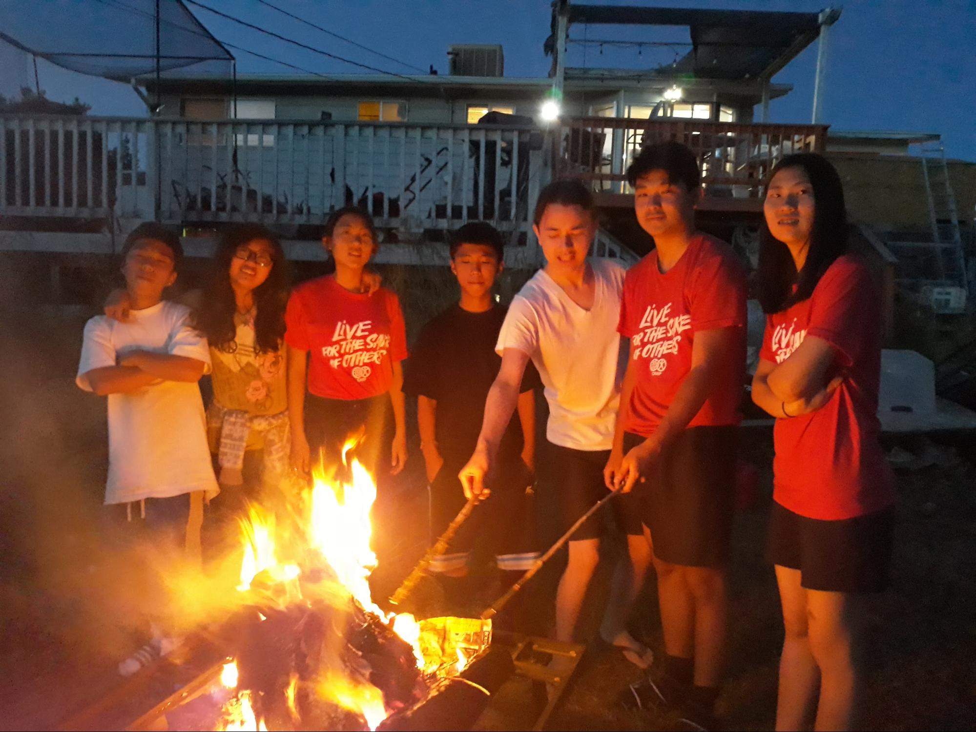 Several participants of the retreat roast marshmallows around the fire pit before joining in a devotional song session.