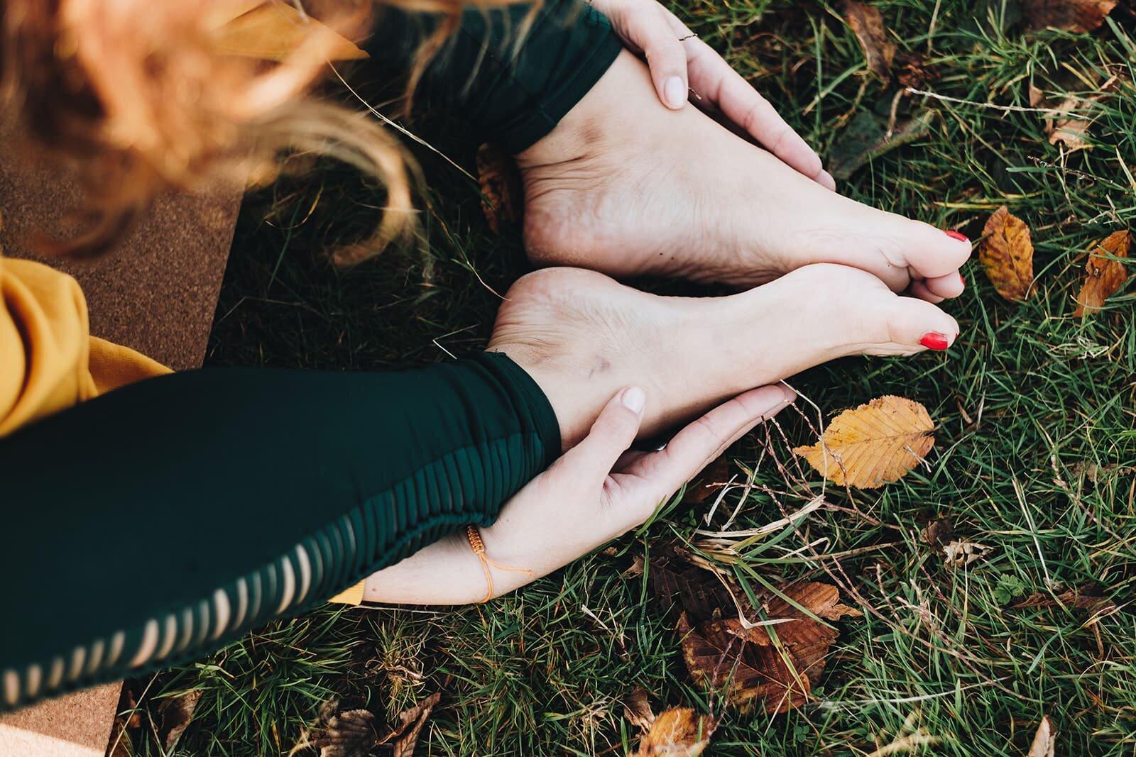 Detalle de pies en una postura de yin yoga en el parque