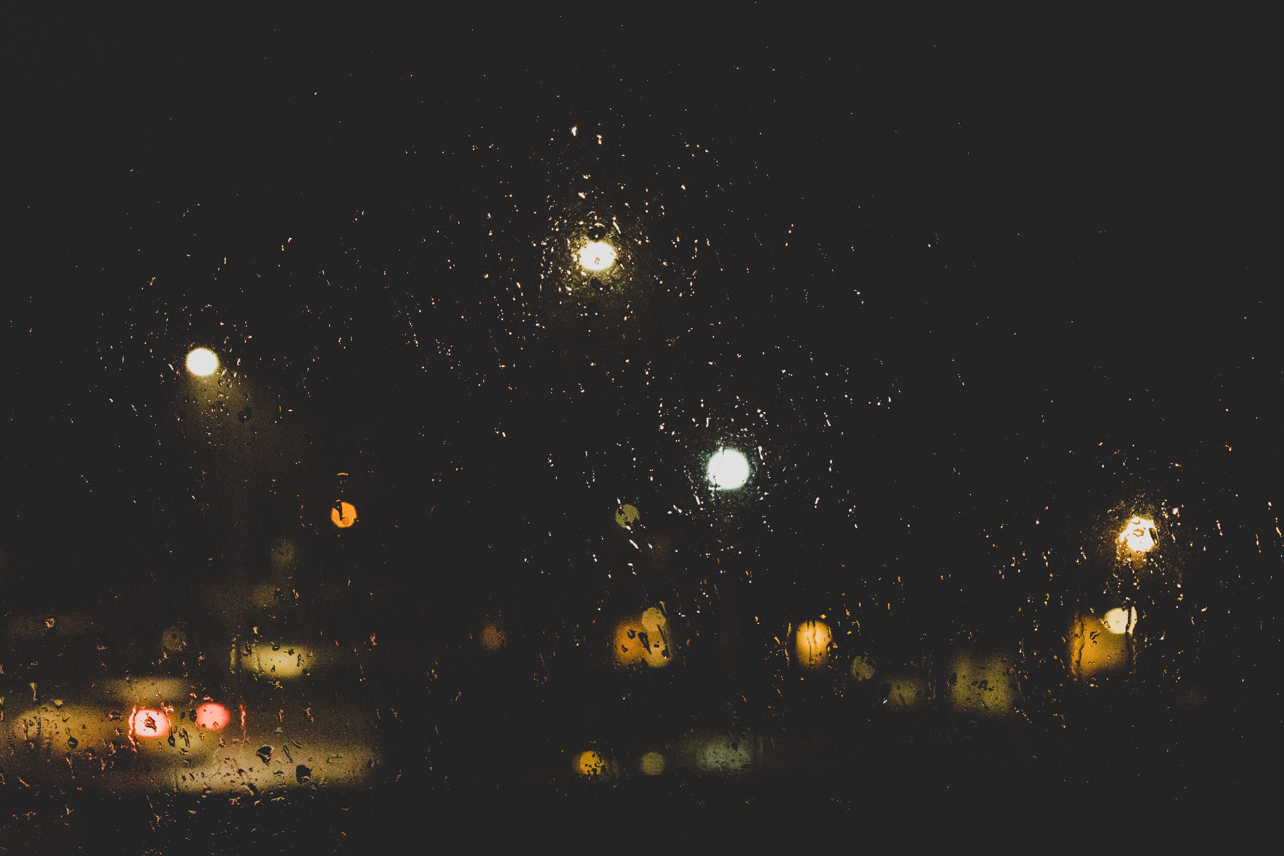 Blurry raindrops on, and cars passing by, a window