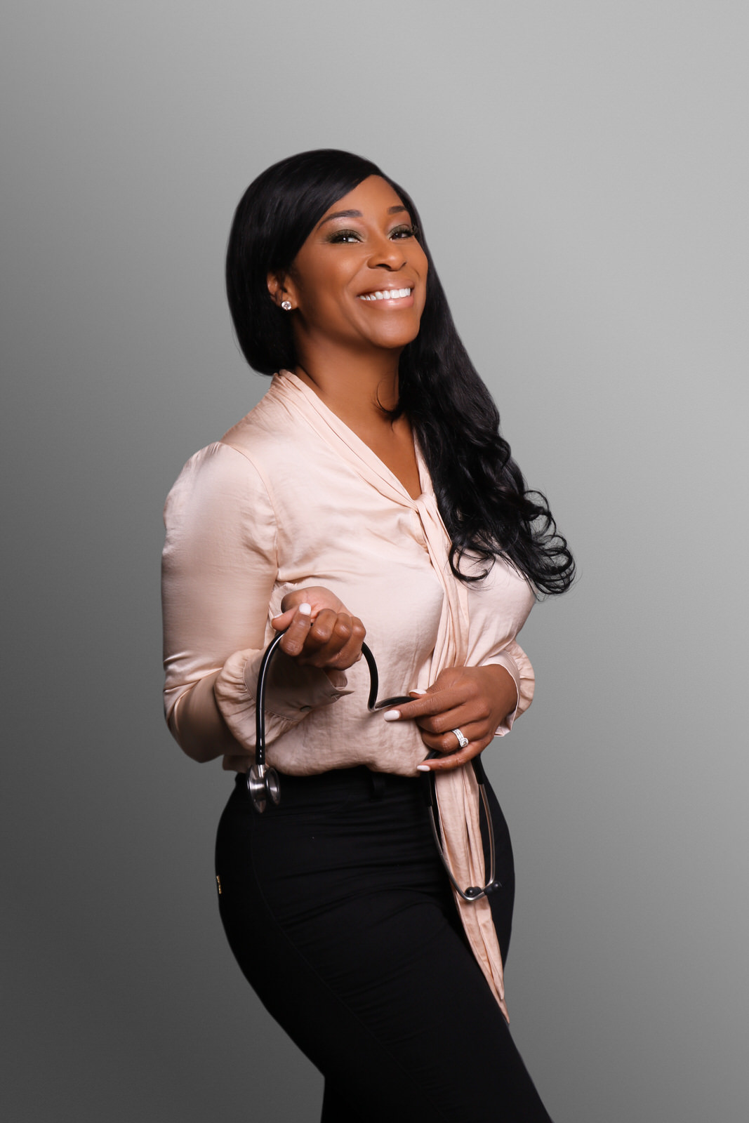 African-American woman in beige blouse and black pants holding stethoscope, gray background.jpg