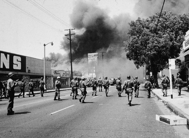 Armed National Guardsmen march toward smoke on the horizon during the Watts riots in Los Angeles, California, August 1965. (Photo by Hulton Archive/Getty Images)