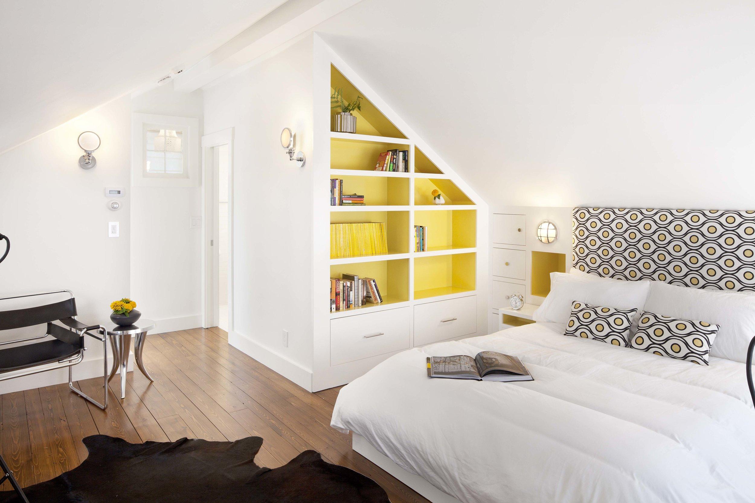 White bedroom with yellow bookshelf detail.