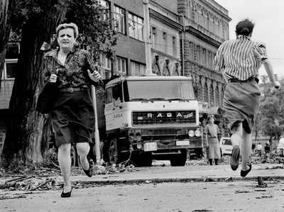"""In this photo from 1992, women run across """"Sniper Alley"""" under the sights of Serb gunmen during the siege of Sarajevo.   Tom Stoddart/Getty Images from NPR story"""