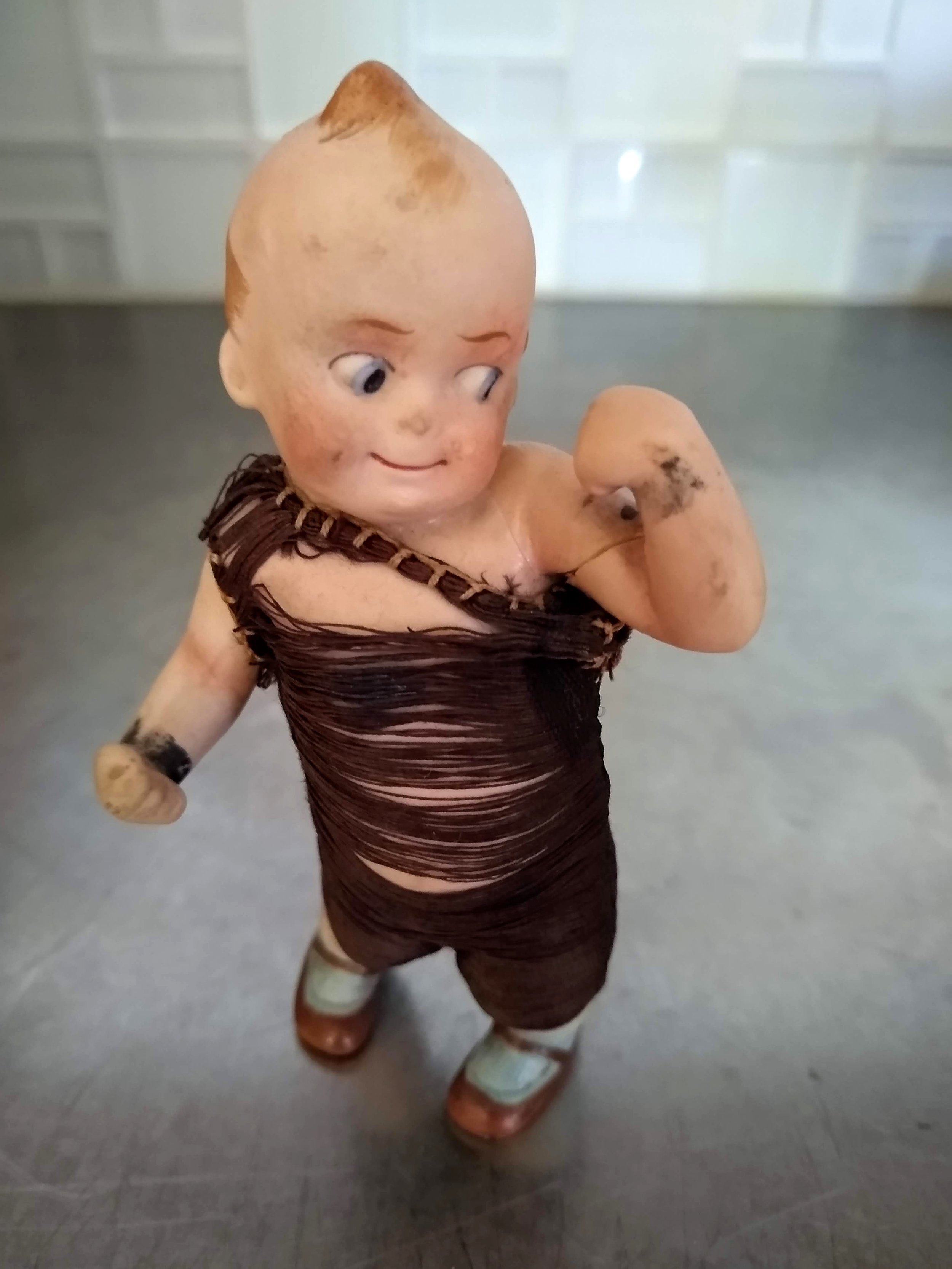 Kewpie dolls were based on a popular cartoon. The bisque figurines were first produced in Germany in 1912 and remained popular in the twenties. This poor little guy is battered and a bit broken, but it's a miracle he survived.