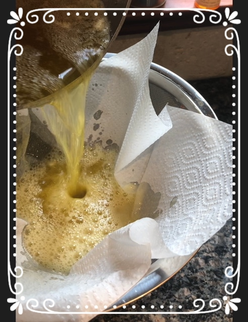 pouring ghee into strainer lined with paper napkin.jpg