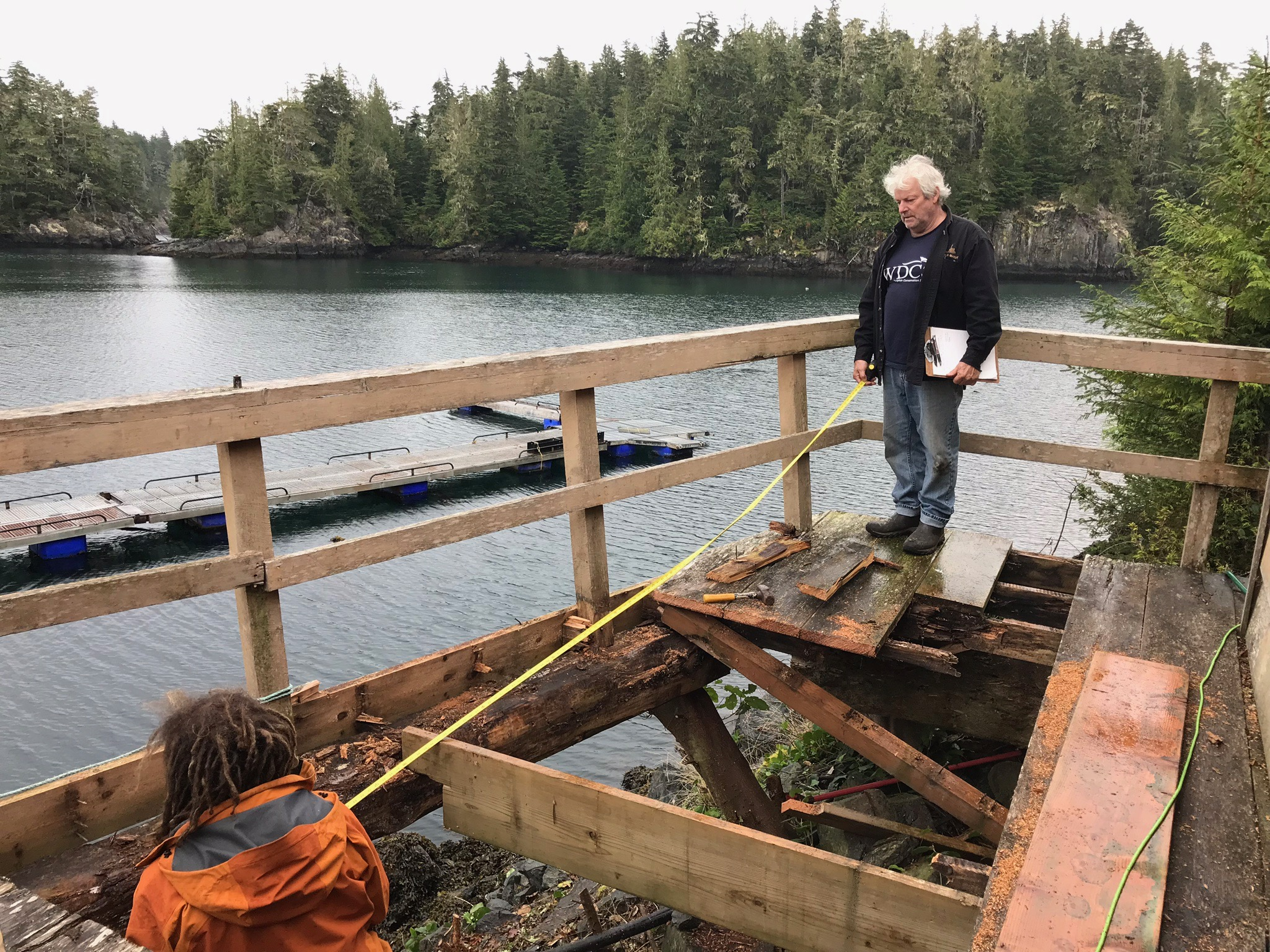Mike Durban with clipboard, and Matchu Preville, working on the rotted out front deck of the lodge.