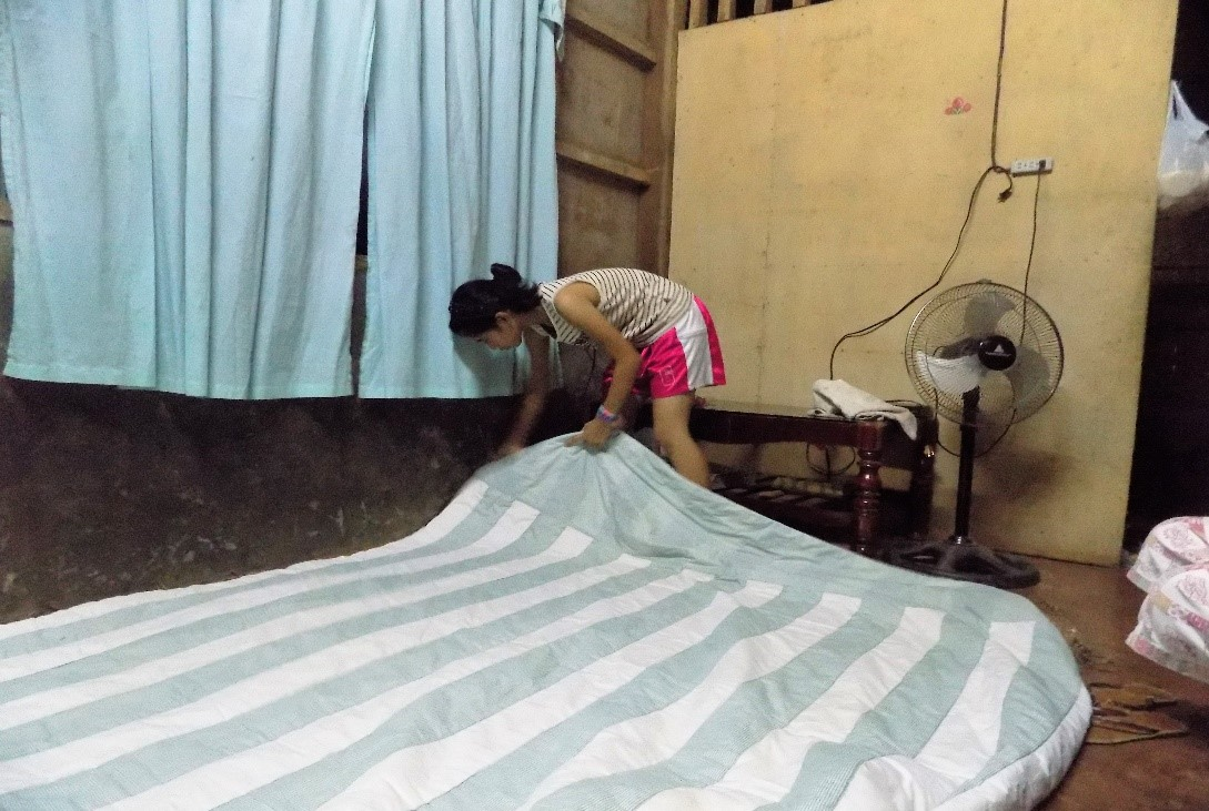 Kimberly is getting her bed ready to sleep.