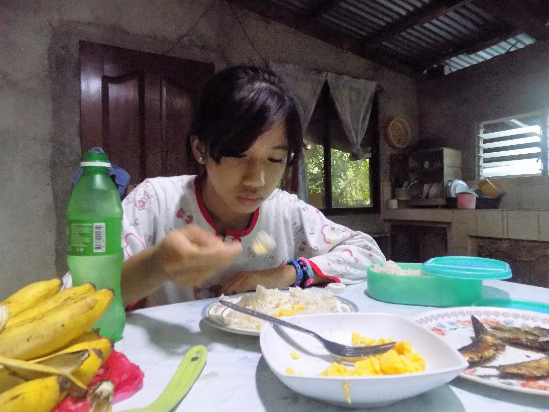 Kimberly delightfully eats the foods her mother prepared for breakfast.