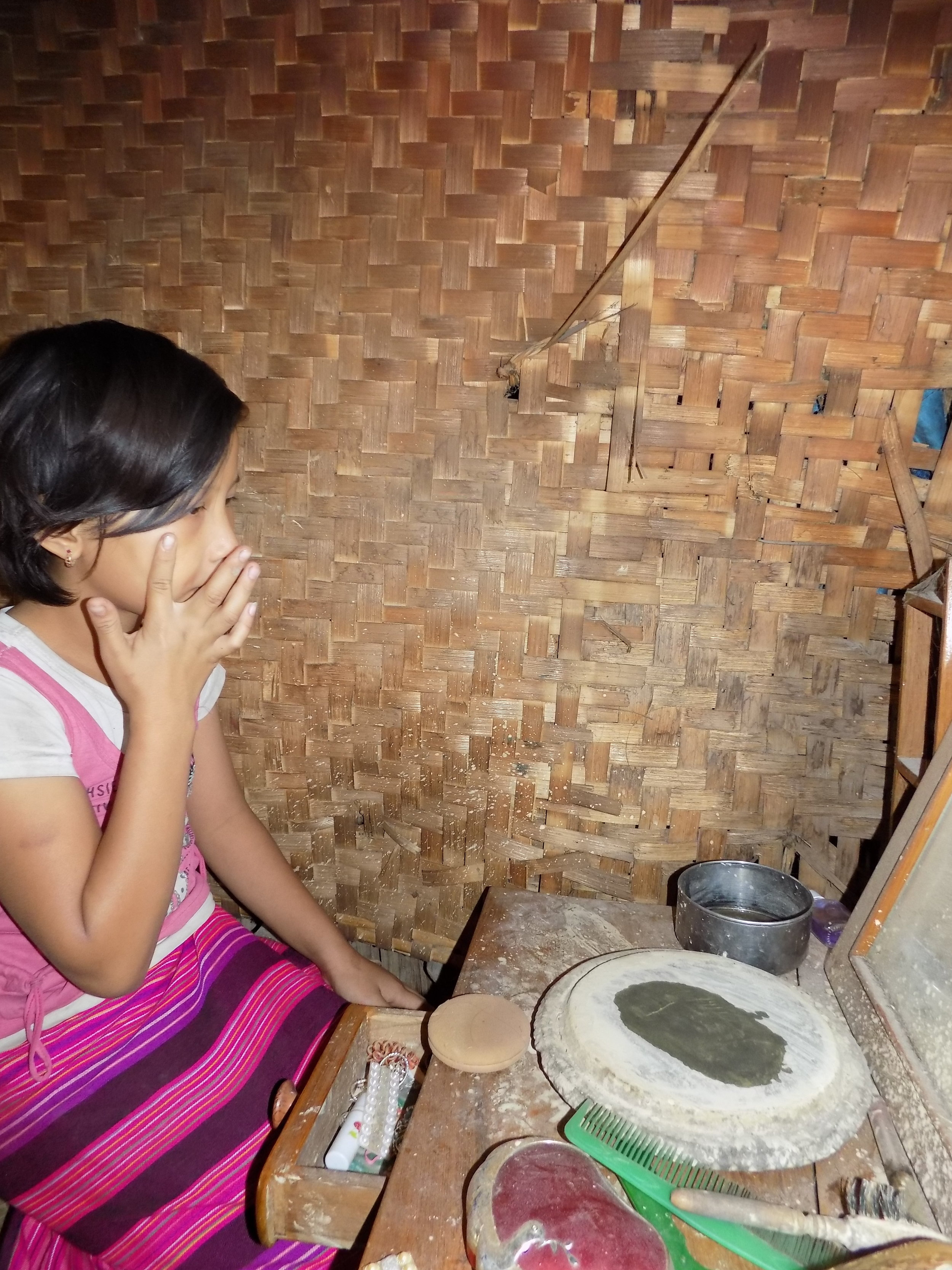Nung Lao Ngun washes her face and then puts on a makeup called Thanaka. It is used as a sunscreen and helps improve one's complexion and keep the skin cool.