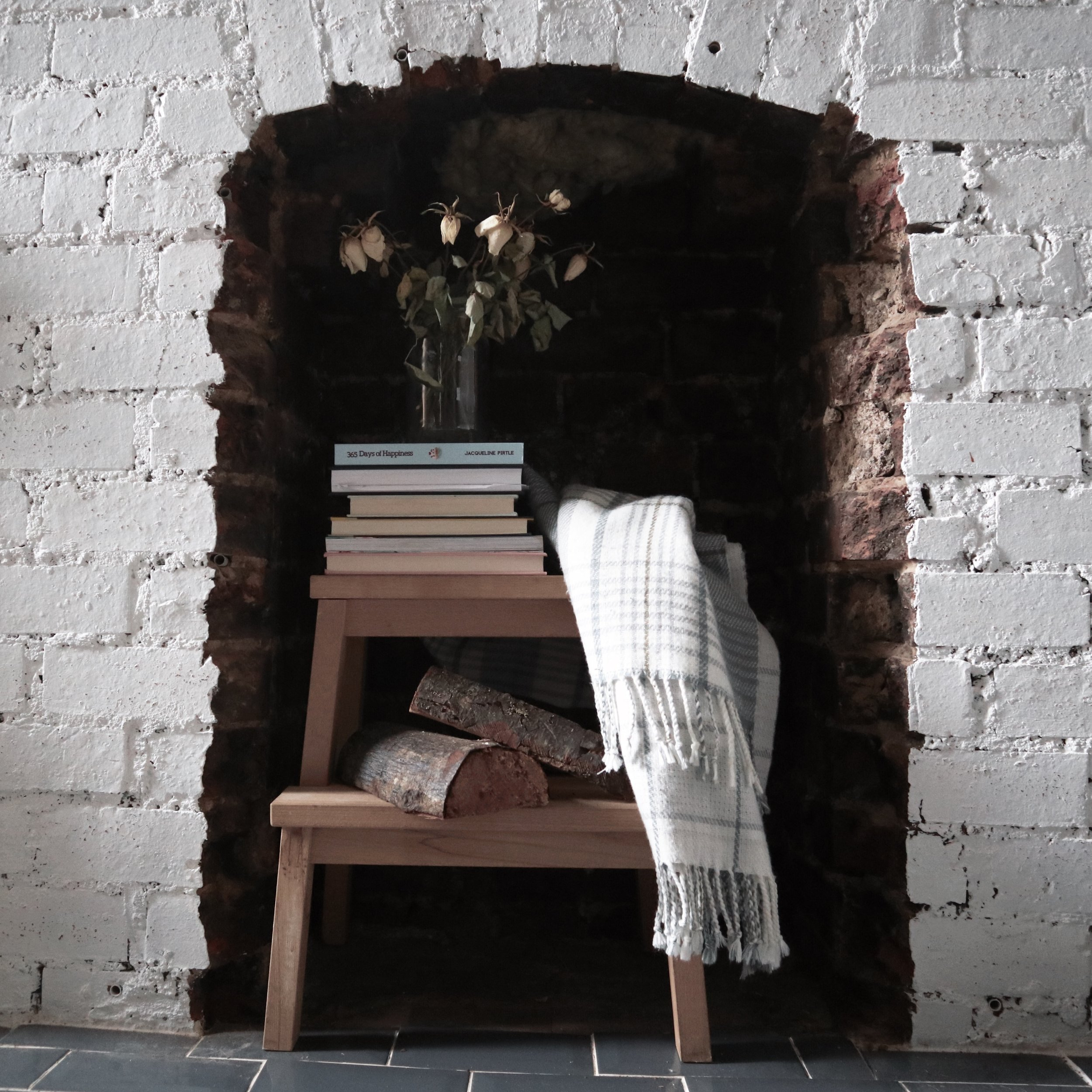 Books on stool in fireplace with rug