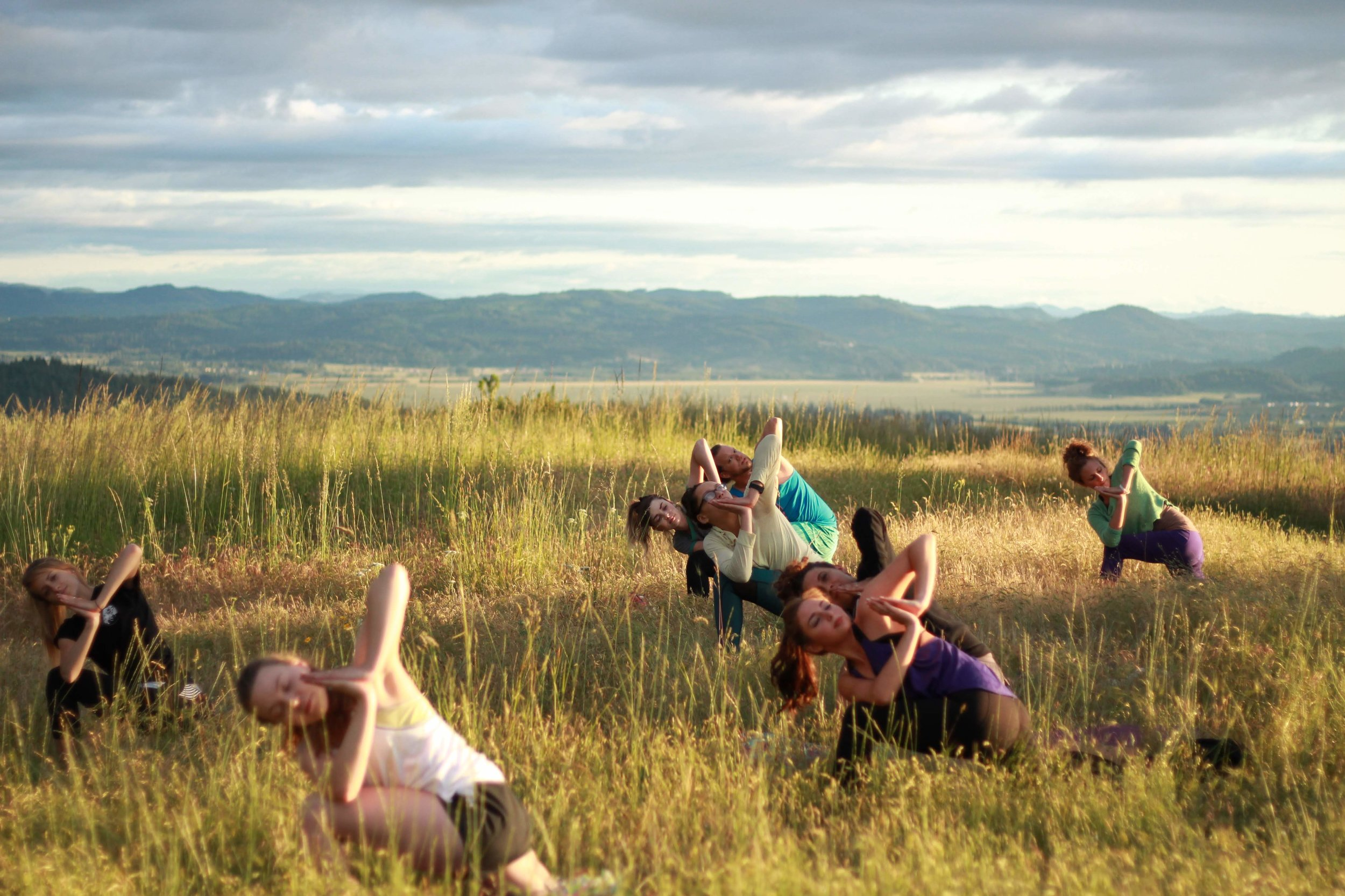 A group of yogis practicing namaskar parsvakonasana at the top of Mt. Pisgah. Photo by @lanceswithwolves