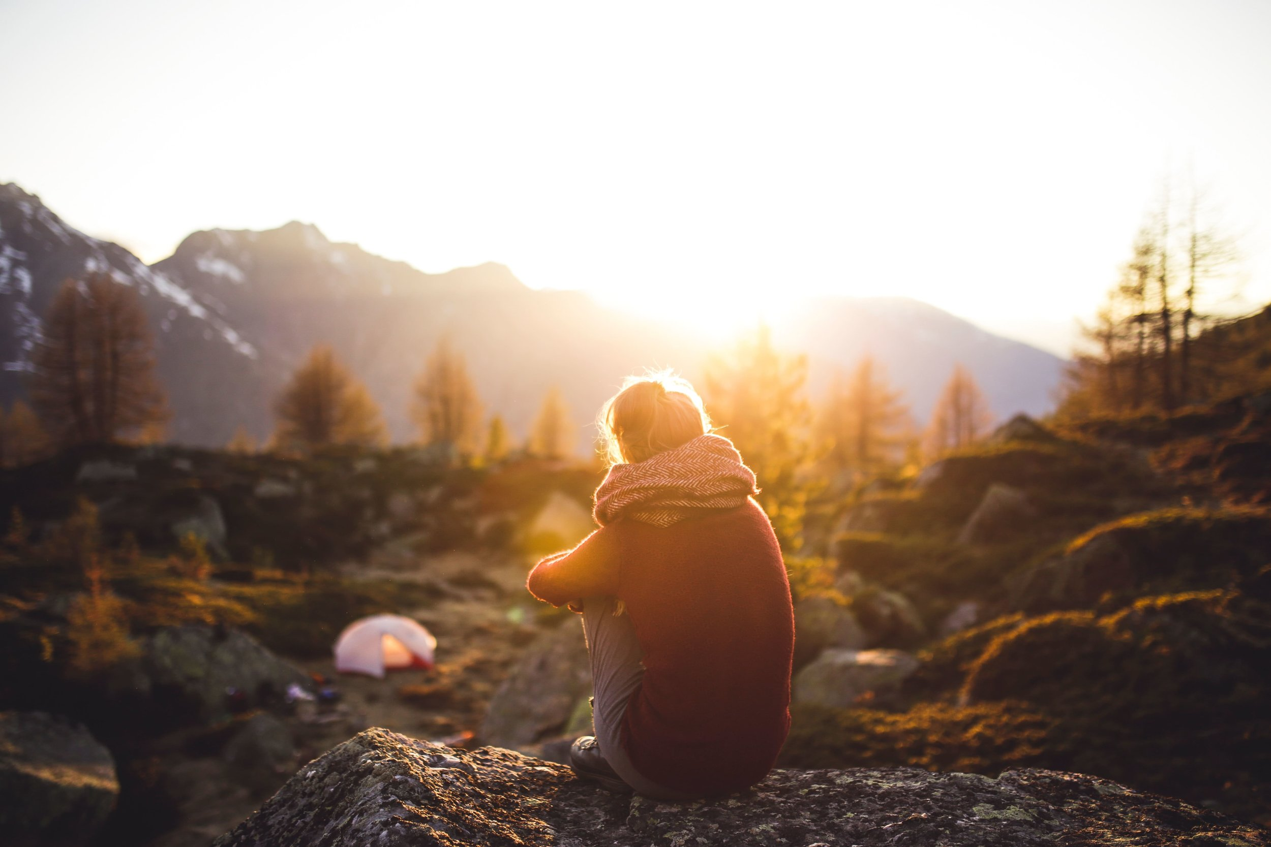 girl sitting alone in nature at sunset