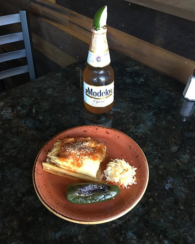 """Today's special! Vegetarian chuchitos, these are Guatemalan/Salvadorian style maize dough tamales wrapped in dried maize husk, the filling is """"loroco"""" a herbaceous edible flower topped with a little salsa and cheese, the obvious pairing an ice cold modelo 😉 . . . . . . #eatlocal #waltham #moodyst #guatemala #guatemalteco #elsalvador #familyowned #authentic #cook #foodie #boston #bostonfoodies #mitierra #chuchito #vegetarian"""