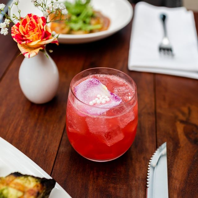 There is no better way to spend your afternoon than with this cocktail in hand! The Aurora is a perfect combination of Dripping Springs Vodka, rose water, raspberry, lemon juice and Waterloo soda! Garnished with a candied rose petal.  #Cocktails #HappyHour #Do512 #Austin