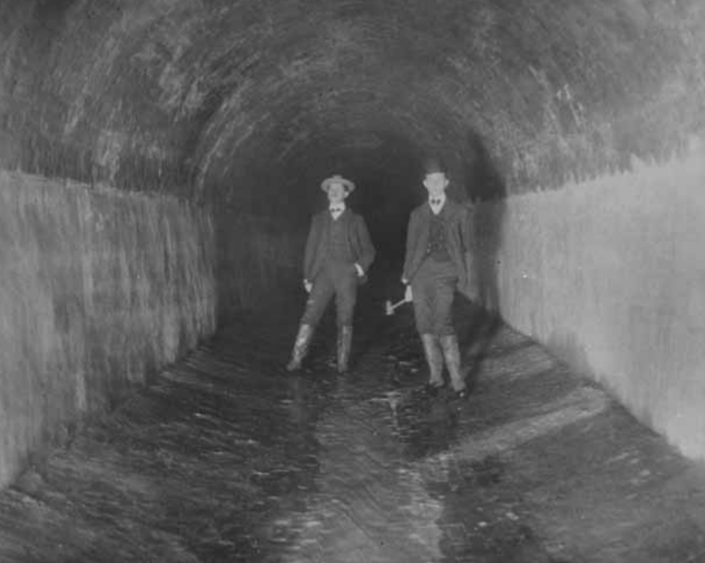 Two visitors pose inside the completed Lydecker Tunnel. Photo:   Washington Star  /Public Domain