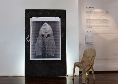 Image: Lily Hibberd, Benevolent Asylum (installation view), board, photographic print, chair, paper, tape, featuring Silence Hood from Old Melbourne Gaol Museum Collection, Fremantle Arts Centre, WA, 2011.