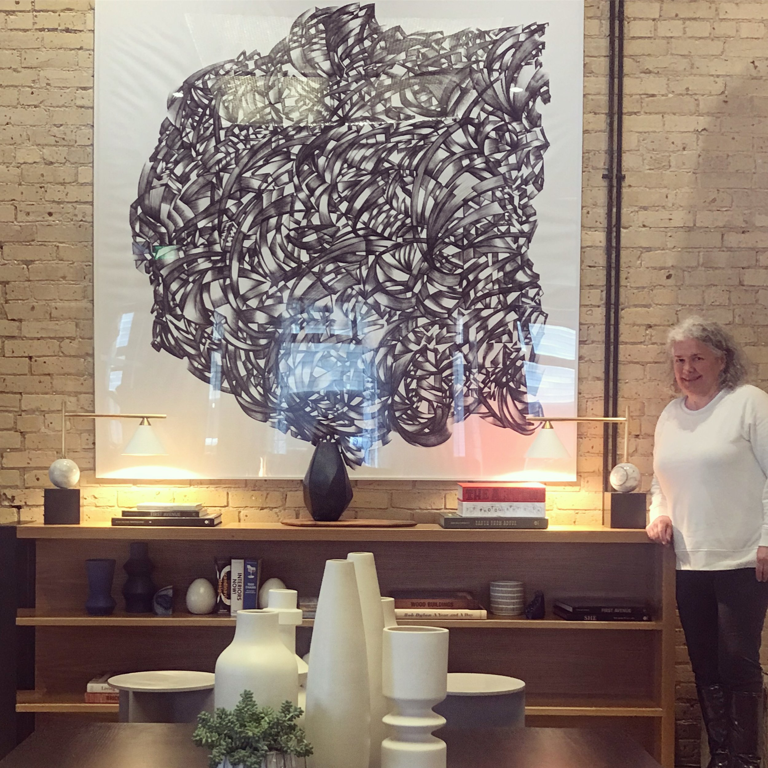 Gretchen in front of her 6' print of one of her line drawings at the new Canopy By Hilton Mill District in Minneapolis