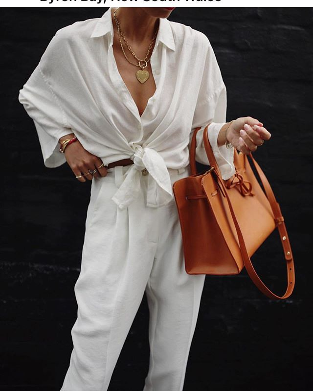Love the all white and casually comfy chic..remember tying our shirts like this years ago? I used to do it all the time. Everything comes back around!! Also, fab pop of color with the handbag. So simply beautiful. @andicsinger