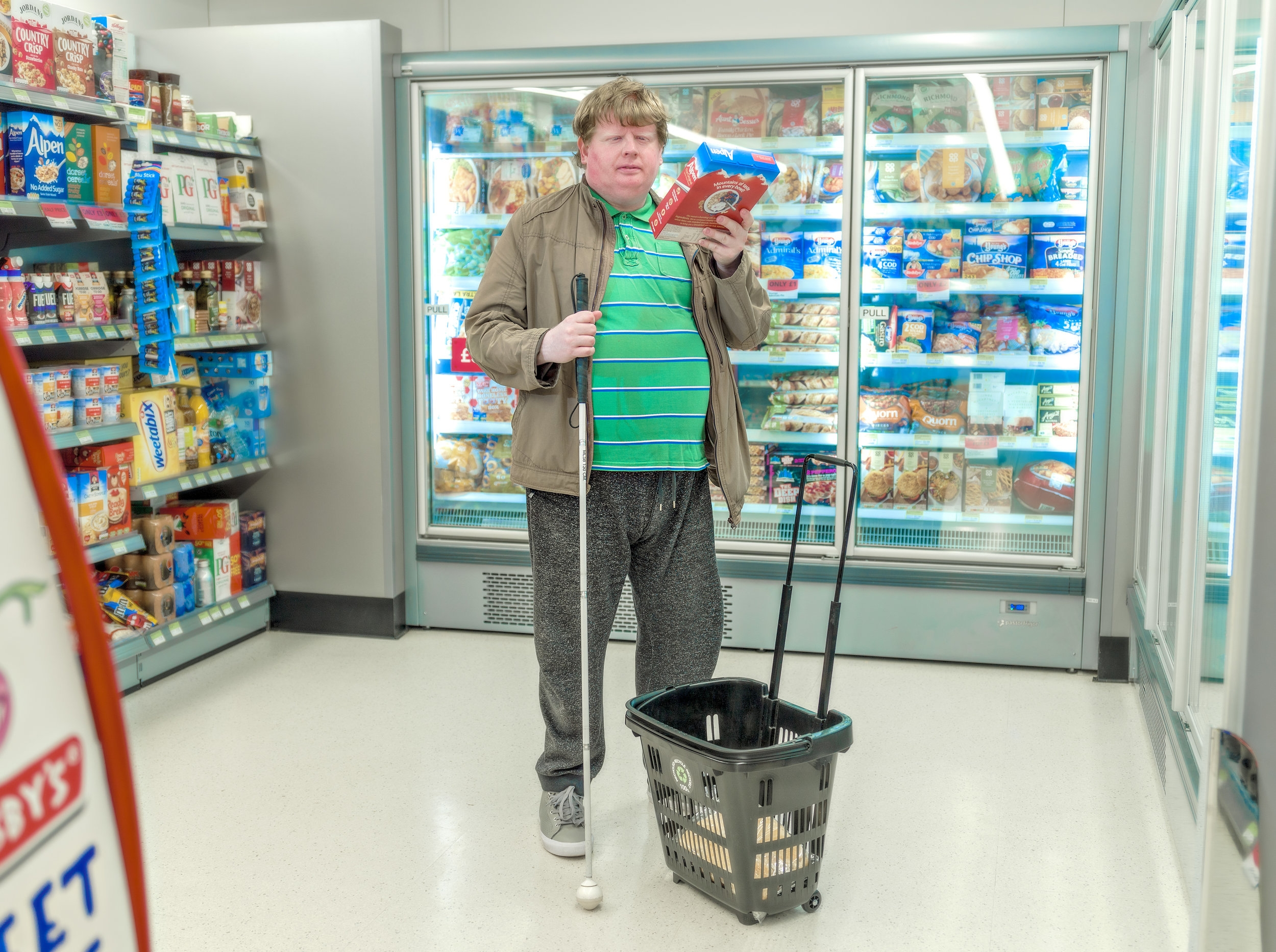 """Justin Rumsby photographed holding his favourite package of cereal at his local supermarket which is routinely moved to different sections around the store making hard for him to find. Ipswich. This image was selected in the British Journal of Photography's 2018 """"Portrait of Britain"""".  http://gallery.portraitofbritain.uk/portrait-of-britain-book-available-for-pre-order-now/"""