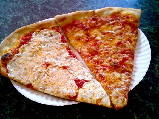 New York-Style Pizza - New York-style pizza, which originated in New York City in the early 1900s, evolved from Neapolitan-style pizza (from Naples, Italy). Historically, it was cooked in a coal-fired or coal-powered oven and its characteristics include a large, hand-tossed thin crust, which is crisp along the edge but still pliable enough beneath its toppings to be folded in half when eaten. (That's how true New Yorkers eat their pizza. Just ask Jon Stewart when he explained this in this classic clip from The Daily Show that still cracks us up 7 years later).Traditional toppings for a New York pizza are a thin later of tomato sauce and dry, shredded, full-fat mozzarella. But NY definitely does pepperoni well, if you're up for some spicy peps.The average New York pizza pie is 18 inches in diameter and is typically cut into 8 fantastically wide slices. Pizza by the slice is a staple in New York and it's remarkably easy to find affordable slices, despite how pricy NYC can be. In fact, there are tons of $0.99 or $1.99 slice spots scattered throughout the city. And the pizza is actually good.New York-style pizza can be found in the New York Metropolitan Area, including in New York (state), Connecticut, New Jersey and throughout the U.S.FANGATING™ TIP: Never eat New York pizza (especially if you're in NYC) with a fork and knife. It's just plain wrong. If the pizza is too hot to pick up, have some beer. And then pick it up, fold and eat at will.
