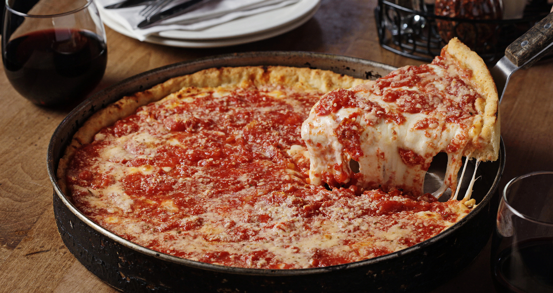 Chicago-Style Deep Dish Pizza - According to Chicago's official cultural historian, Tim Samuelson, there's no one person who is officially credited with having invented Chicago-Style deep dish pizza. It is said the recipe was first conceived at Pizzeria Uno in 1945 by its founder, Ike Sewell. Others say that it was Uno's aforementioned pizza chef, Rudy Malnati, Sr., who created it.History aside, what makes deep dish unique is—as its name certainly implies—is its deep (or high-edged) crust, which when filled with pizza ingredients such as chunky tomato sauce and copious amounts of melty, gooey cheese, begins to resemble more of a pie, or even a stuffed pizza, far more so than it resembles a flatbread (of Neapolitan fame). While the pie might appear to be a pure gut bomb (and don't confuse what we're saying, because it totally is), the crust itself is actually of only thin to medium thickness.Deep dish Chi-Town pizza is characteristically round as it is baked in a round, steel pan similar to one you might use to bake a cake or a pie. (Think springform pans). The pan is well oiled (à la Detroit style), which helps make the pizza easy to remove and which also gives the outside of the crust a fried effect.When you take a bite of a good deep dish pizza, you may notice that the crust tastes a bit sweet. That's because in addition to using a run-of-the-mill (see what we did there?) wheat flour, some pizzerias use corn meal or semolina, which provide a sweeter—and more yellowish in color/tone—flavored crust.Another noteworthy characteristic of Chicago-Style deep dish pizza is that it usually appears upside down. Rather than having the sauce atop the dough, and then the cheese and toppings, deep dish is made with the cheese (often sliced mozz) melted onto the crust first. The cheese is then covered with toppings, such as pepperoni or sausage (which forms a nice patty-like layer) or veggies such as peppers, onions and mushrooms. Then comes the sauce, which is uncooked and is o
