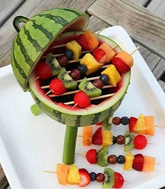 "A watermelon that resembles a barbecue! - A Memorial Day cookout isn't complete without sweet summer fruit. And what a way to serve it!This grill was made with fruit skewers stacked with: canteloupe, pineapple, strawberries, blueberries, grapes, kiwi, and raspberries. (And don't forget the blackberries! They make the ""charcoal"" in the bottom!) And you can find wooden skewers at most grocery stores or online."