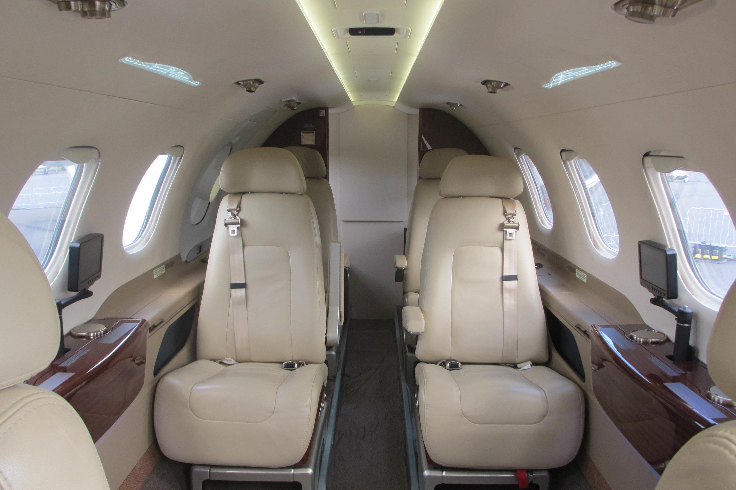 Interior of an Embraer Phenom 300 light jet. Above banner: Bombardier LearJet 45.