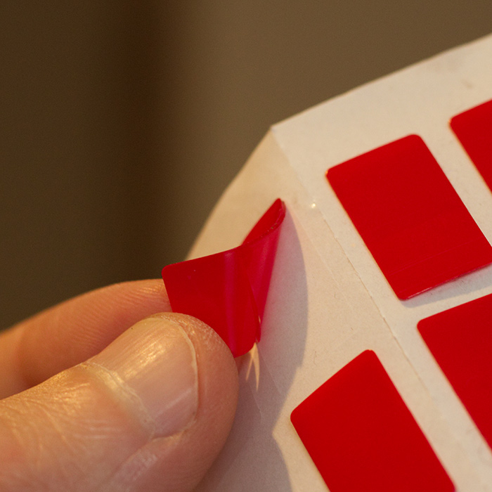 1. Remove SAVVYSTAY from backing sheet, using red tab -