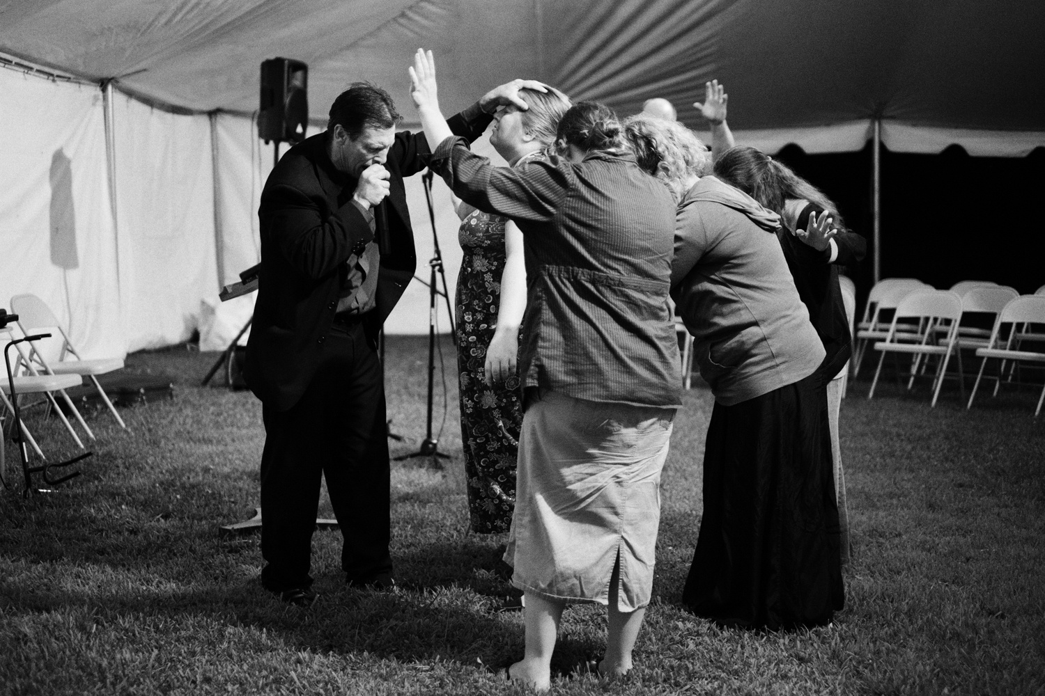 Roger May . August 2, 2014. Preacher Roger Stevens prays for a woman at a tent revival in Baisden, Mingo County, West Virginia.