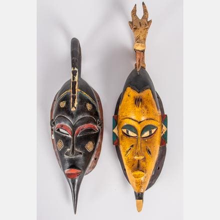 TWO IVORY COAST WOOD GURO MASKS   Two Ivory Coast Carved and Painted Wood Guro Masks, 20th Century, Including a scorpion and antelope mask. Largest dimensions: h: 25 1/4 in.   Estimate: $80 - $120