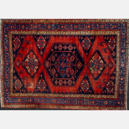 NORTHWEST PERSIAN WOOL RUG   20th Century, having a hexagonal center medallion on a navy field   Estimate: $800 - $1,200