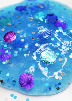 mermaid-themed-slime-in-teal-blue-decorated-with-blue-and-silver-glitter-flakes-and-tiny-shell-shapes-in-purple-turquoise-and-blue-metallic-colors.jpg
