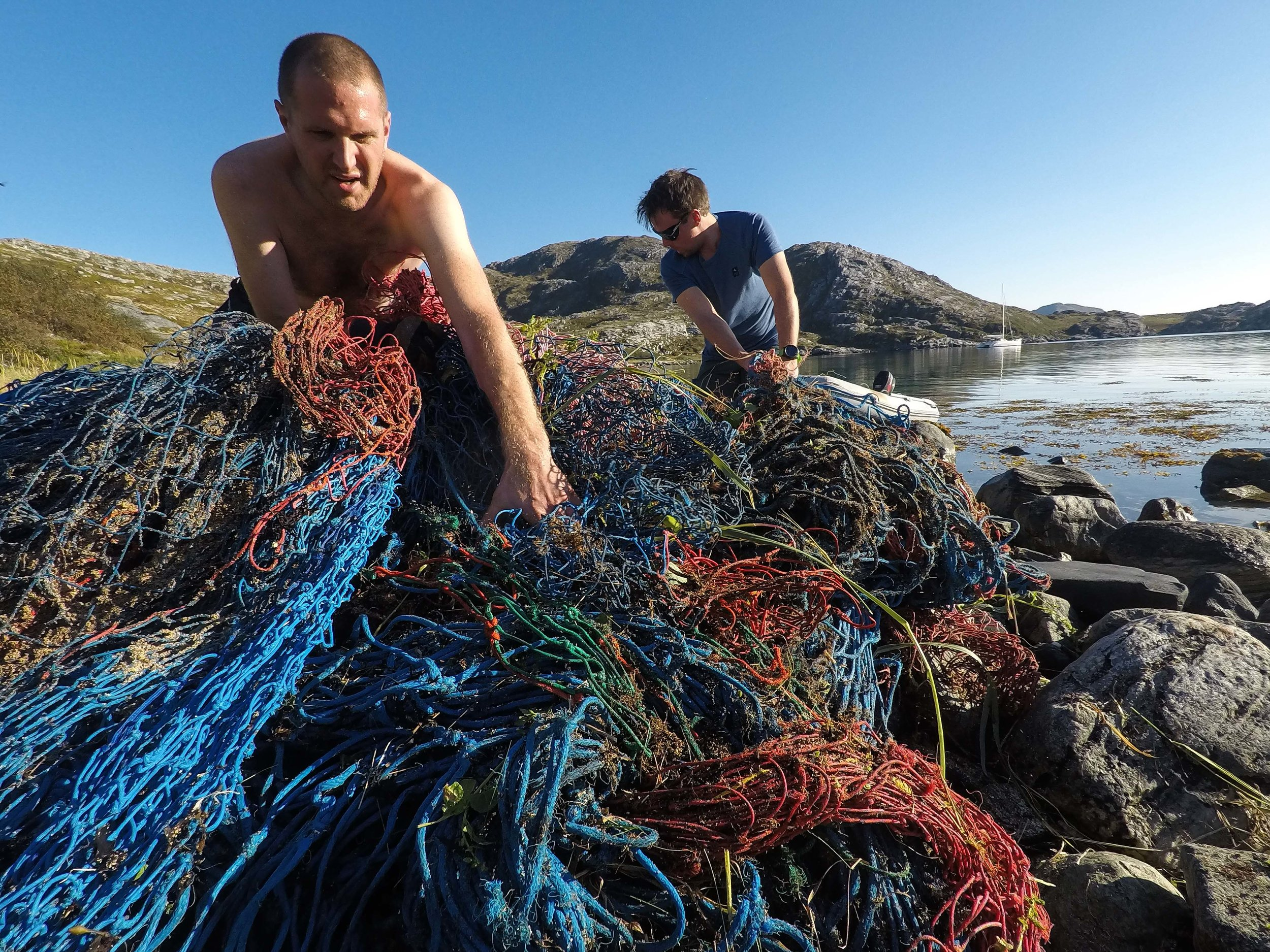 Volunteers Brieuc and Andreas working hard to remove a 200 kg plastic fishing net from the marine environment around the island Andammen, at 70°N. Photographer: Jonas Legernes